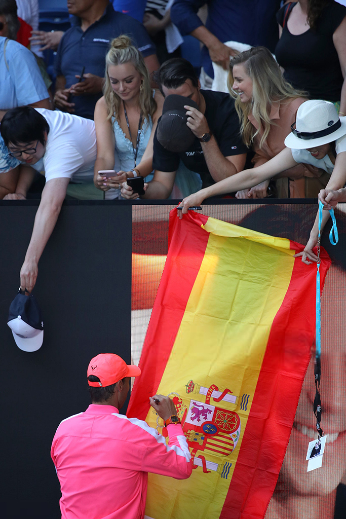 MELBOURNE, AUSTRALIA - JANUARY 25: Rafael Nadal of Spain signs autographs for fans after winning his Men's Singles third round match against Pablo Carreno Busta of Spain on day six of the 2020 Australian Open at Melbourne Park on January 25, 2020 in Melbourne, Australia. (Photo by Mark Kolbe/Getty Images)