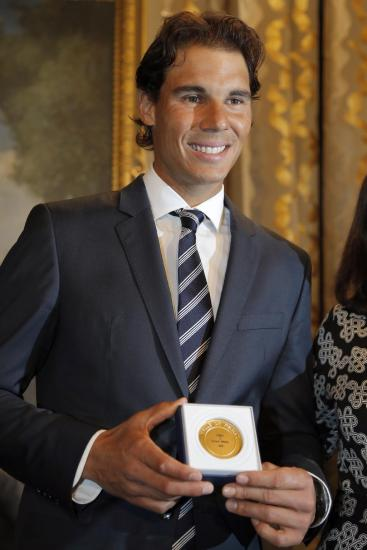 Tennis player Rafael Nadal poses with the Grand Vermeil Paris medal, after receiving it from Paris Mayor Anne Hidalgo during a ceremony at the Paris City Hall, Thursday, May 21, 2015. By winning the 2014 French Open, Nadal became the only male player to win a single Grand Slam tournament nine times and he begins defense his title on the upcoming French Open at Roland Garros stadium next week. (AP Photo/Francois Mori)