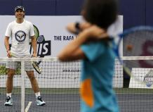 Spanish tennis player Rafael Nadal (L) plays tennis with a child during a 'tennis clinic' of his Rafa Nadal Academy with Filipino children in Manila, Philippines, 06 December 2015. Nadal is in Manila with other current and former international male and female tennis aces to compete in the International Premier Tennis League (IPTL). (Tenis, Filipinas) EFE/EPA/FRANCIS R. MALASIG