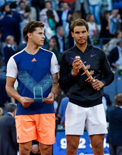 Spanish tennis player Rafael Nadal (R) and Austrian tennis player Dominic Thiem pose with their trophies at the end of their ATP Madrid Open final match in Madrid, on May 14, 2017..Nadal won 7-6 and 6-4. / AFP PHOTO / OSCAR DEL POZO (May 13, 2017 - Source: AFP)