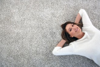 Upper view of woman relaxing on carpet at home