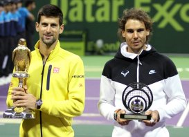 Novak Djokovic (L) of Serbia holds the trophy as he stands next to second place Rafael Nadal of Spain after winning his Qatar Open men's single tennis final match in Doha, Qatar, January 9, 2016. REUTERS/Naseem Zeitoon