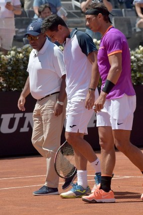 Rafael Nadal of Spain (R) helps Nicolas Almagro of Spain forced to abandoned after an injury during their match at the ATP Tennis Open tournament on May 17, 2017 at the Foro Italico in Rome. / AFP PHOTO / TIZIANA FABI (Photo credit should read TIZIANA FABI/AFP/Getty Images)