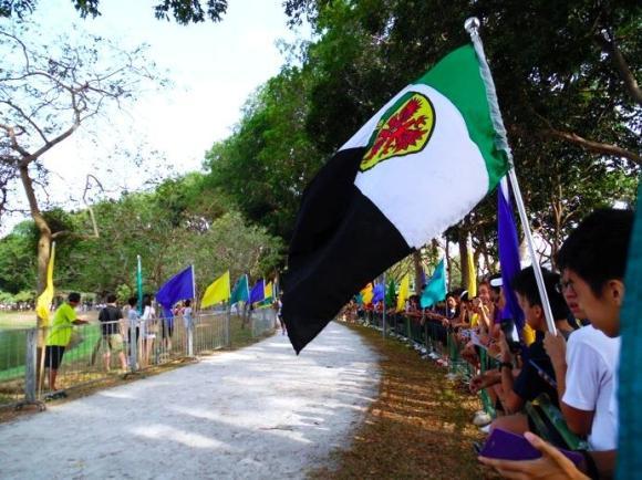 The RI flag flies high; audiences crowd along the barricades near the finish line.