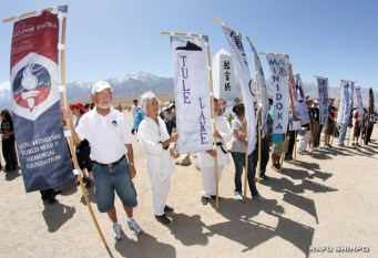 Banners representing the 10 former relocation centers and other groups were flown at the conclusion of the ceremony. From left, Bill Shishima, Ernie Jane Nishii and Nanncy Oda (partially obscured). The number of attendees was estimated at more than 800.