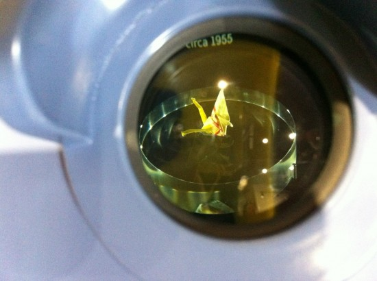 Sadako Sasaki's paper crane as seen through a magnifying glass at a new exhibit at World War II Valor in the Pacific National Monument at Pearl Harbor. (Pacific Historic Parks)