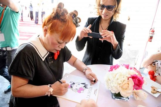 Musician Yoshiki takes a photo as Sanrio head designer Yuko Yamaguchi draws a cartoon for him.