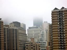 Fog encapsulates tall buildings.