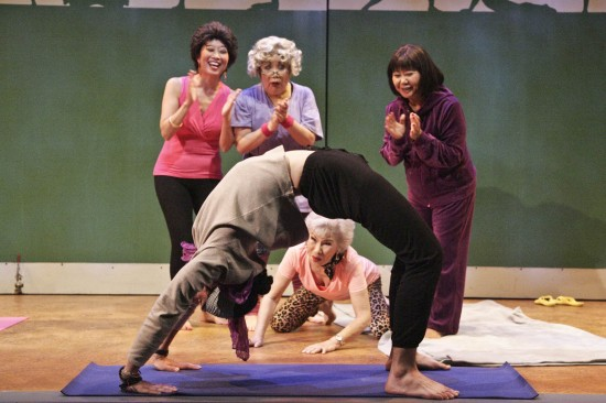 """The Nisei Widows are amazed at yoga teacher Patrick's bridge pose. From left: Jeanne Sakata as Tomi, Tui Asau as Patarick, Emily Kuroda as Hana, June Kyoko Lu as Betty, and Takayo Fischer as Sumi in East West Players' """"The Nisei Widows Club: How Tomi Got Her Groove Back."""" (Photo by Michael Lamont)"""