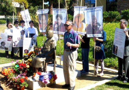 Phil Shigekuni speaks next to the comfort women monument as rally participants hold up photos of surviving comfort women.