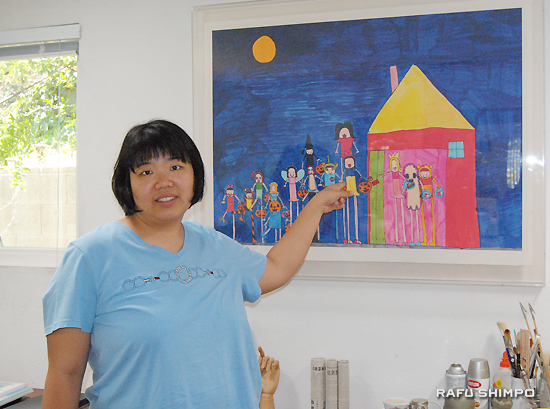 Hikaru Fong points to her favorite artwork, which she drew about her Halloween trick-or-treat experience. (RYOKO NAKAMURA/Rafu Shimpo)