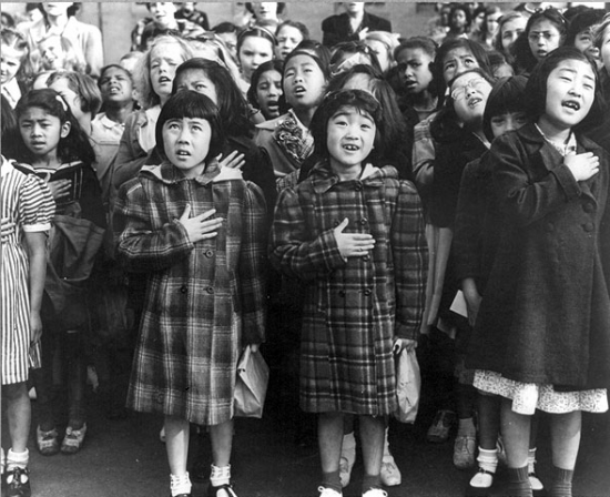 San Francisco, April 1942. Children from the Weill public school, from the so-called international settlement, shown in a flag pledge ceremony. Some of them are Japanese Americans who will be interned for the duration of the war. (Photo attributed to Dorothea Lange, part of U.S. War Relocation Authority collection)