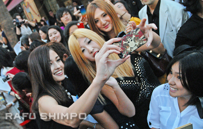 """Meisa Kuroki, who stars as Fujiko Mine in """"Lupin the Third,"""" poses for a photo with fans, on the red carpet at Friday's opening of EigaFest. (MIKEY HIRANO CULROSS/Rafu Shimpo)"""