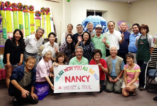 """Kikuchi's friends at the L.A. Tanabata Festival send a message of encouragement. The sign reads, """"We are with you all the way Nancy. Heart and Soul."""" At the L.A. Tanabata Festival, which Kikuchi co-chaired, volunteers wore bright pink shirts in her honor."""