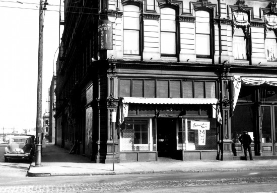 """Teikoku Company, owned by the Matsushima Family. Sold Japanese groceries and general merchandise from 1905 to December 7, 1941. Reopened for the """"Evacuation Sale"""" and closed when the family had to report to the Portland Assembly Center. The brick Christmas decorations are still remaining in the window display. NW 3rd and Davis, Nihonmachi, Portland, Oregon, ca. 1942. (Courtesy Oregon Nikkei Legacy Center)"""
