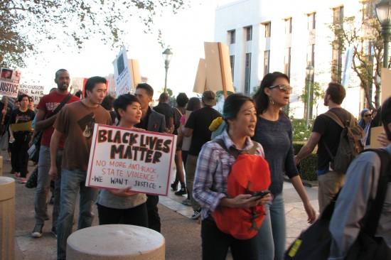 Traci Ishigo (holding sign) participates in a protest of the Ferguson decision in downtown Los Angeles on Nov. 26.  (J.K. YAMAMOTO/Rafu Shimpo)
