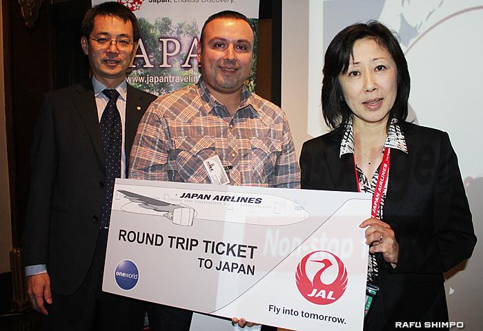 抽選に当たりJALの栗原支店長(左端)と森永営業部長(右端)から日本行きの往復航空券をプレゼントされたセミナー参加者(中央)