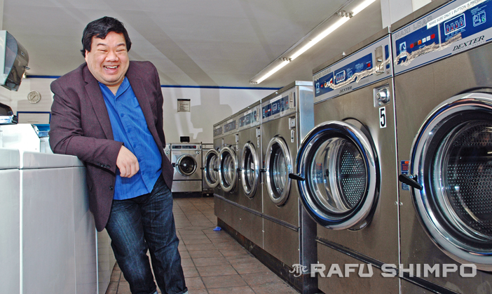 """Peter Kuo laughs amongst the suds and spin cycles in South Pasadena on Tuesday. He is directing the latest from East West Players, the comedy """"Washer/Dryer."""" (MIKEY HIRANO CULROSS/Rafu Shimpo)"""