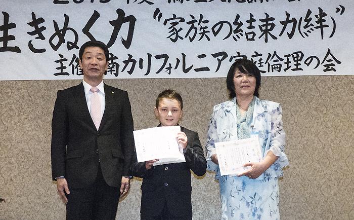 8日に行われた「倫理文化講演会」の場で、同研究所生涯局教育企画部部長の藤崎正剛氏(左)から賞状を授与された松浦さん(中央)。右は、バレー学園の摺木先生
