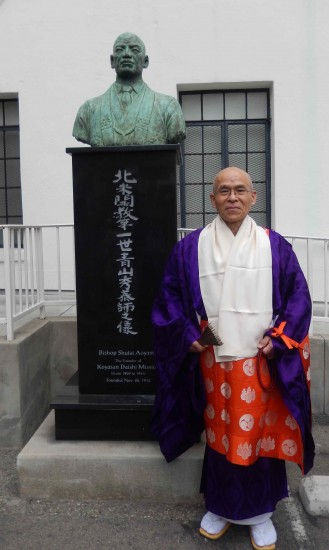 Rev. Junkun Imamura in front of a bust of Bishop Shutai Aoyama, founder of Koyasan Daishi Mission.