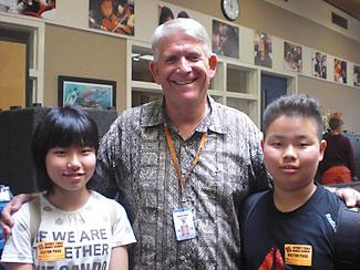 中学の校長先生(中央)から歓迎を受ける福留さん(左)と宝満さん(右)
