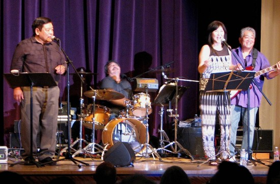 The Music Co. featured Randy Yoshimoto on drums, Dane Matsumura on bass, and vocalists Howie Hiyoshida and Mariko Nishizu.