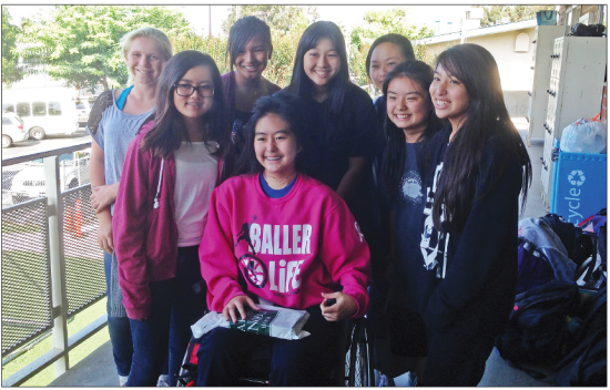 Kelli Sakaguchi visits with schoolmates before returning to classes at First Lutheran School in Torrance, after being partially paralyzed in an auto accident last summer.