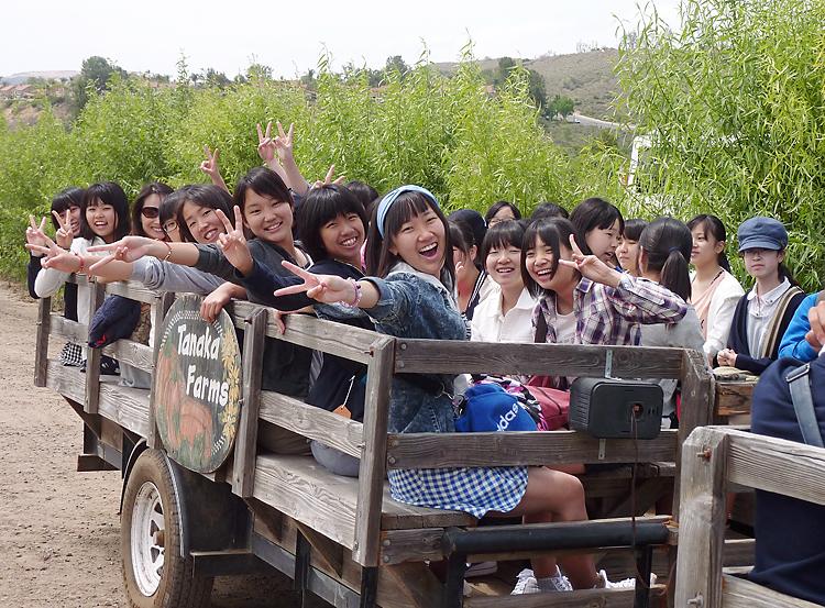 トラクターの荷台に乗ってタナカ農場を回る生徒たち
