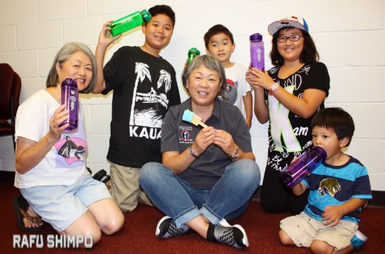From left: Trish Nicholson, Higashi Obon dance instructor, Calvin Kamimura, Janet Ito, Corey Kamimura, Katey Kamimura and Grant Hashimoto hold recyclable drinking bottles that will be sold at the Higashi Honganji Obon carnival this weekend. Each bottle sells for $3 and includes a drink coupon worth $2. (GWEN MURANAKA/Rafu Shimpo)