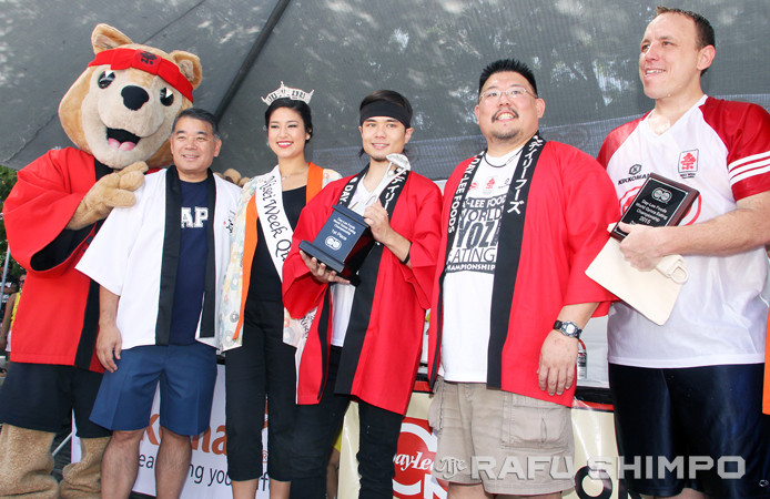 The champion accepts the trophy on stage with Aki the Akita, Terry Hara, 2015 Nisei Week Queen Sara Hutter and Day-Lee Foods' Jason Uno. (MARIO G. REYES/Rafu Shimpo)