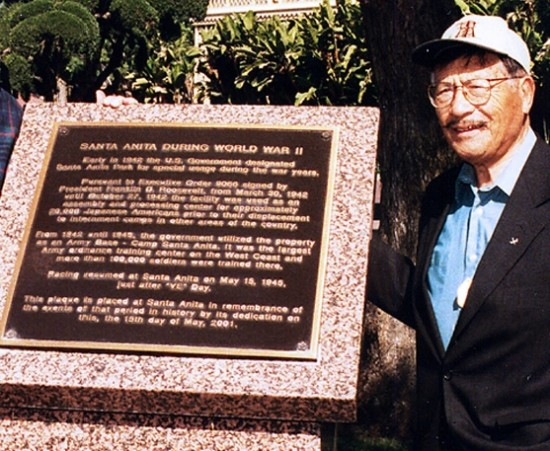 Yoshinaga poses next to a plaque dedicated to the Santa Anita Assembly Center.