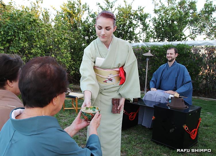 日本庭園で行われた立礼席で、正客の米国書道研究会会長の生田愽子さんにお茶を出すステファニー・ワトソンさん(中央)。右奥は、亭主のポール・ニューカムさん
