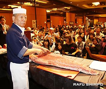 JRAが主催する日本食の試食イベントで、大きなマグロを捌く豊島さん