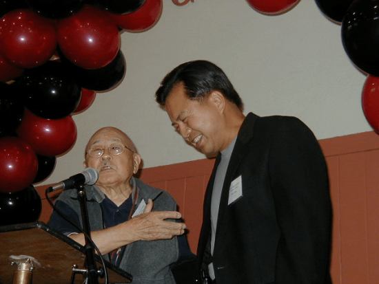 Fred Hoshiyama, pictured with sportscaster Rick Quan, spoke at a Buchanan YMCA celebration in San Francisco in 2004. He helped re-establish the branch after World War II. (Hokubei Mainichi)