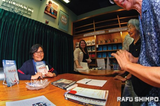 """Naomi Hirahara poses for a photo with her latest work in the Mas Arai mystery series, """"Sayonara Slam,"""" during an author reading and discussion at Vroman's Bookstore in Pasadena on May 2. (MIKEY HIRANO CULROSS/Rafu Shimpo)"""