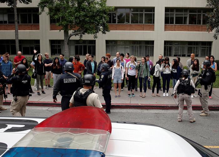 警官の指示の従い避難する学生ら