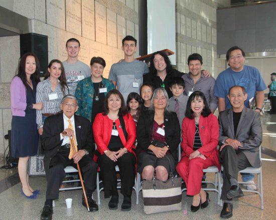 Speakers at the Min Yasui centennial tribute and Yasui family members. Front row, from left: Norman Mineta, Peggy Nagae, Holly Yasui, Karen Korematsu, Dale Minami. Middle row, from left: Julie Yan Yasui, Elif Cik Yasui, Robin Yasui, Leyla Yasui, Naomi Yasui, Julian Yasui. Back row, from left: Caleb Haas, Lucas Haas, Tim Yasui, Todd Yasui, Tyra Fujikura. (Photo by Bacon Sakatani)