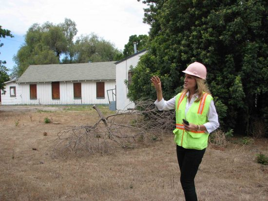 Mary Urashima of the Historic Wintersburg Preservation Task Force leads the tour. In the background are the church buildings.