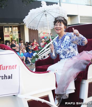 今年のグランド・マーシャル、佳緒里・奈良・ターナーさん。白馬の馬車に乗って登場