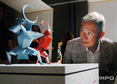 """George Takei examines two of the origami character figures used in """"Kubo,"""" during an event last Thursday at JANM. Takei donated the figure of his character, Hosato, to the museum's collection. (MIKEY HIRANO CULROSS/Rafu Shimpo)."""