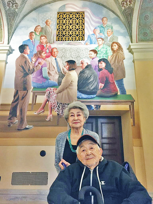 """George Yamaguchi and his wife Florence pose in front of the mural """"We the People, Out of Many, One"""" at Bob Hope Patriotic Hall in April 2016. A rendering of George can be seen in the upper right corner, with Hope's hand on his shoulder Veteran and actor John Fujioka is depicted in the upper left part of the work. (Photos courtesy Georgiana Yoshioka)"""