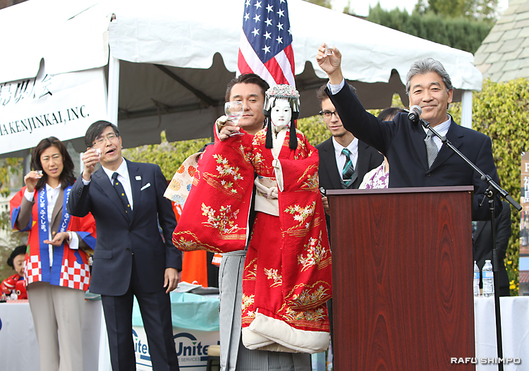 乾杯の音頭をとる南加日系商工会議所次期会頭のジェフ山崎さん(右)。左の人形もグラスを掲げ、参加者を喜ばせた