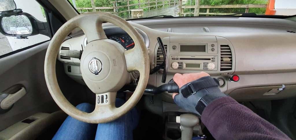 foto van auto-aanpassingen in de vorm van handbedrijfsrem en handgassegment ingebouwd in Nissan Micra van een autorijschool
