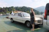 Mercedes-Benz W116 op de pont van het Como Meer tussen Menaggio en Bellagio Italië met daarbij de trotse eigenaresse