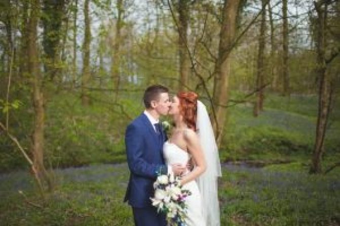 bride and groom kissing in bluebells at heskin hall