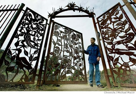 """gates128_mac.jpg John Sissom, 12 of Berkeley checks out the garden gates. The Peralta Community Garden in Berkey has a grand entry of a metal gate into the gardens. Home and Garden story on, """"Gates"""". Event on 1/28/04 in Berkeley. MICHAEL MACOR / The Chronicle MANDATORY CREDIT FOR PHOTOG AND SF CHRONICLE/NO SALES-MAGS OUT"""
