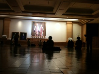 """Church goers intoning in the prayer hall, in front of a larger-than-life portrait of """"True Parents"""""""