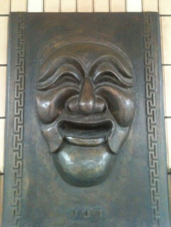 A tarnished metal mask in the walls of the subway.