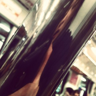 selfie reflected from the support bar in the subway