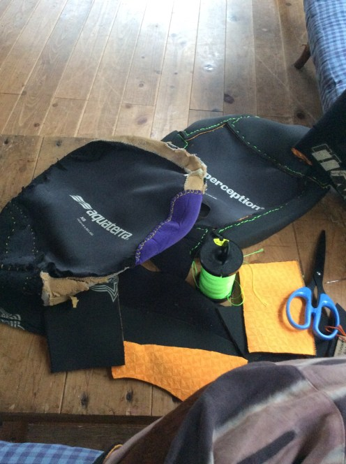 Mending kayak gear with an old wetsuit on a rainy day.